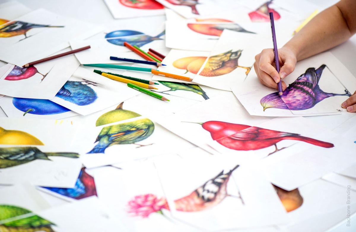 Artista desenhando dezenas de pássaros coloridos com frutas em suas cabeças.