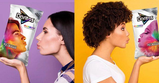 Duas mulheres, uma de costas para outra, segurando pacotes de Doritos com pessoas lgbt coloridas mandando beijos